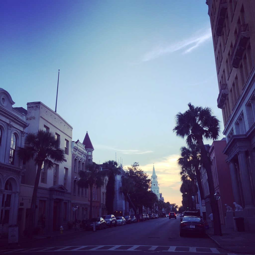 Sun setting behind buildings on street in Charleston